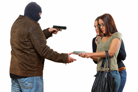 Bad guy is robbering a two young women with a gun 스톡 콘텐츠