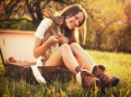 그녀의 토끼와 함께 아름 다운 젊은 여자의 빈티지 스타일 사진 스톡 콘텐츠