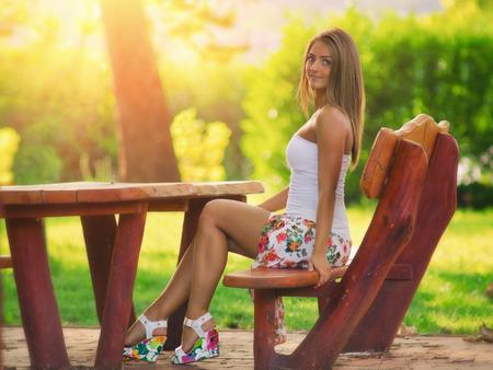 mujer rubia desnuda: Las mujeres atractivas en el parque, puesta del sol en el fondo