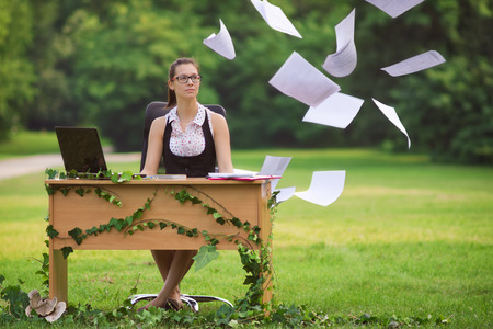 stringent: Office in the nature, happy young secretary throwing documents in the air Stock Photo