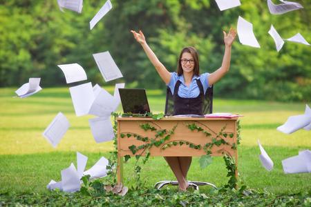 自然の中で空気で書類を投げて幸せな若い秘書オフィス
