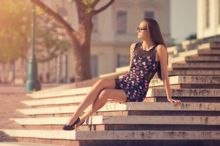 green brown: Beautiful young women enjoying sunlight in the city park