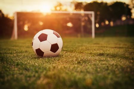 terrain de foot: Football dans le coucher de soleil