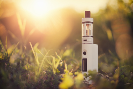 Adjustable electronic cigarette, carcinogenic alternative for Non smoking, sunset in the background