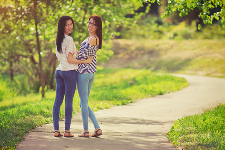 Girlfriends in the park, two young women walking in the walkway Stock Photo