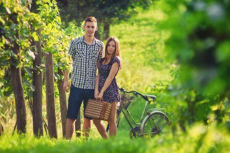 tomando vino: Atractiva pareja en campo Foto de archivo