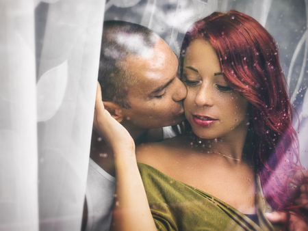 caucasian water drops: Lovers behind a wet window