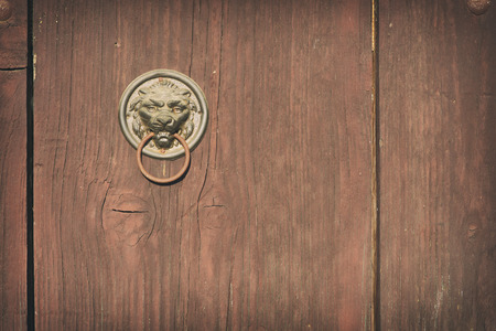 worn structure: Old vintage cellar door wood and decorated with a rusty handle lion head
