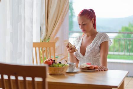 Las mujeres jóvenes ver a su teléfono atractivo y tienen un desayuno en su casa en la mañana Foto de archivo