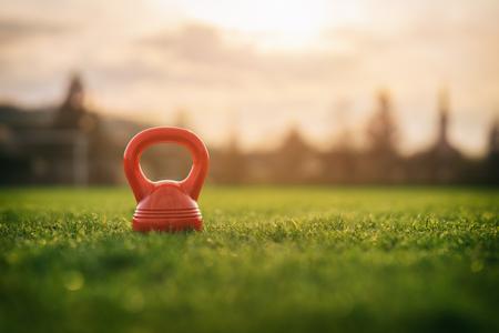 Outdoor foto's uit de kettlebell voor vrouwen op de speelplaats, zonsondergang op de achtergrond