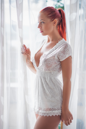 Beautiful young women standing in the balcony in the White Lace Dress