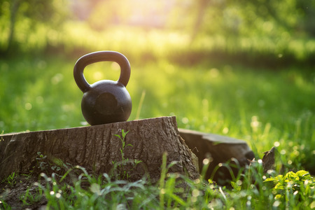 Outdoor photos from the kettlebell in the park, sunset in the background Stock Photo