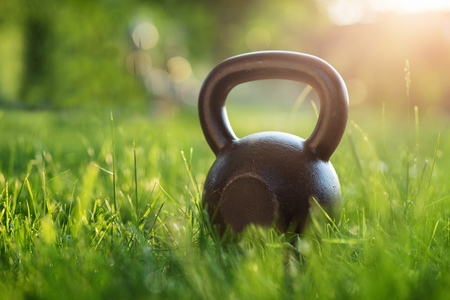 Outdoor photos from the kettlebell in the park, sunset in the background Archivio Fotografico