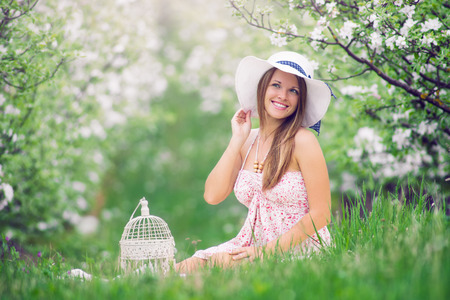fashion dress: Beautiful young girl sitting in the garden at fruit flowering in spring