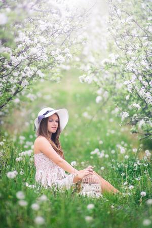 봄 과일 꽃의 정원에 앉아 아름 다운 소녀 photo