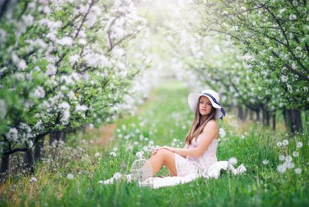 belle brune: Belle jeune fille assise dans le jardin de fruits floraison au printemps Banque d'images