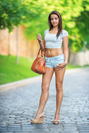 Beautiful young woman walking in the park with a bag