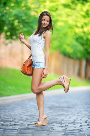 camera girl: Beautiful young woman walking in the park with a bag