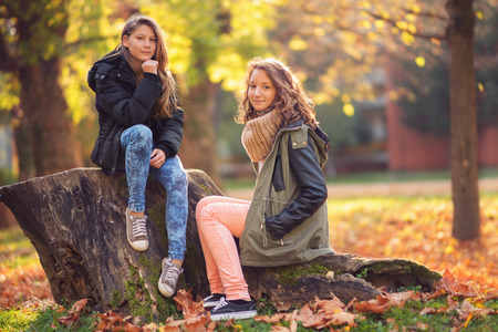 Two young girl in the city park at autumn