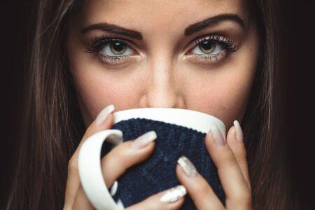 human eye: Closeup photo from a beautiful young woman drinking from mug