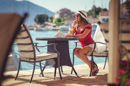 nice weather: Young woman having coffee break in the harbor taverns