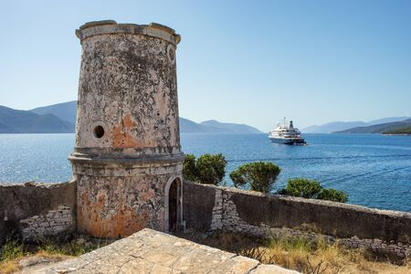 Old lighthouse with a luxury ship in the background, in Kefalonia, Ionian Islands, Greece Stock Photo