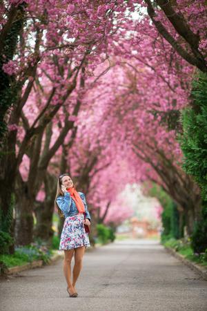 젊은 여자가 봄 꽃에 아름다운 공원에서 그녀의 전화로 얘기 스톡 콘텐츠