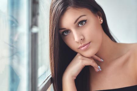 아름 다운 젊은 여자, 창에서 그녀의 반사에서 표시