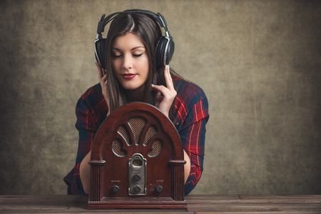 오래 된 라디오와 현대 헤드폰 젊은 여자