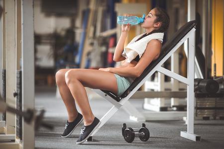 젊은 여자는 무게와 훈련 후 휴식. 빈티지 스타일의 사진과 필름 필터 및 미세 입자 필름 스톡 콘텐츠