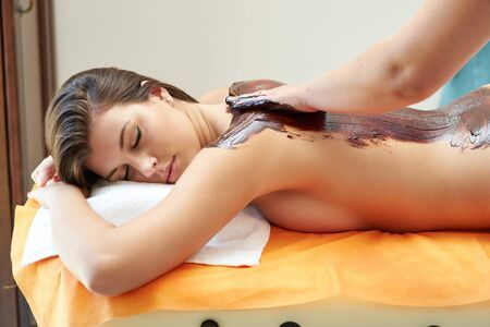 Young woman take a chocolate massage in the spa