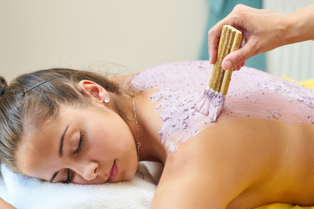 Young woman take a grape-massage therapy in the spa