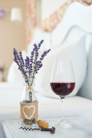 vintage furniture: Red wine and vintage decor vase in a bright bedroom