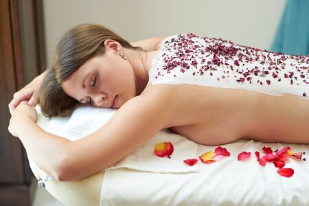 Young woman taking a clay therapy with dried petals in a spa 스톡 콘텐츠