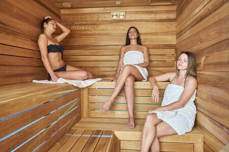 finnish bath: Three young woman resting in sauna Stock Photo
