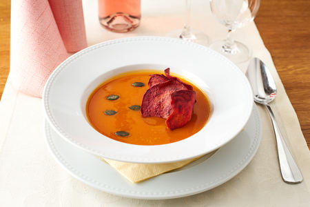 Pumpkin cream soup with ginger and beetroot chips Standard-Bild