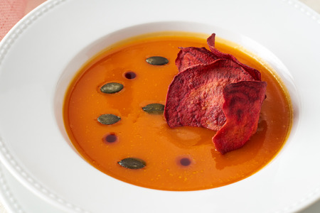 Pumpkin cream soup with ginger and beetroot chips Archivio Fotografico