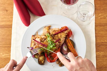 Man cutting a grilled chicken in a restaurant with vegetables Standard-Bild
