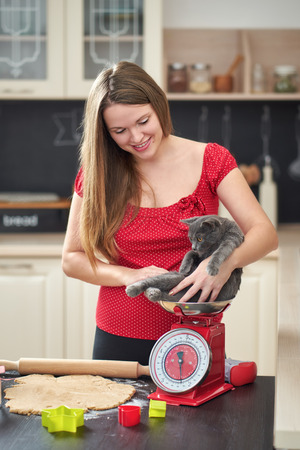 Young woman playing with her cat between baking