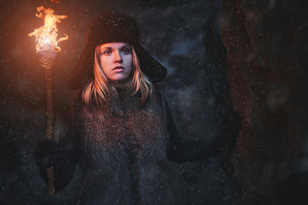 Lost young woman with a torchlight at snowstorm