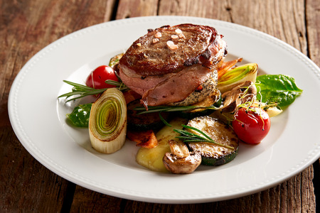 Leg of lamb steak wrapped in bacon with grilled vegetables Archivio Fotografico
