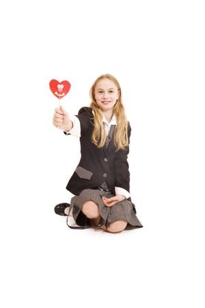 Schoolgirl and a heart shaped lollipop isolated on white photo