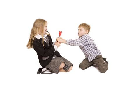 Boy and girl fighting over a lollipop (isolated on white) photo