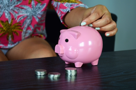 Woman is putting a coin into a piggy bank. Stock fotó