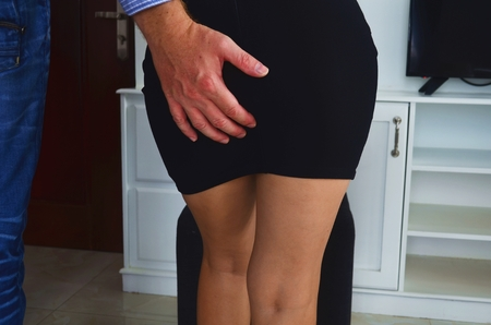 Sexual harassment at work, man is touching the butt of a woman. Stock Photo