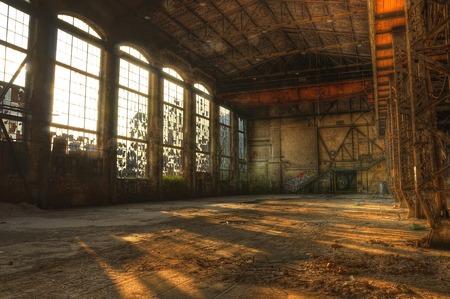 放棄された産業ホールで大きな窓を通って落ちる木漏れ日