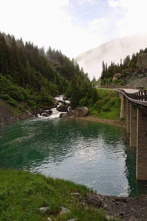 Road to the mountains next to a mountain lake photo