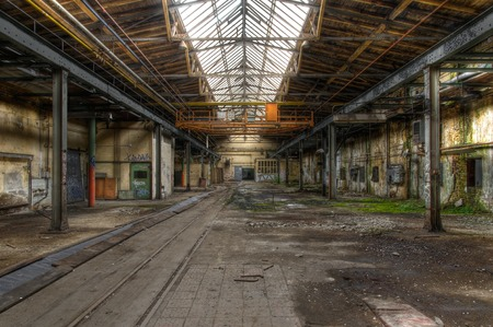 Abandoned hall with large windows and an old crane
