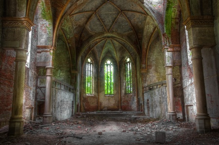 Looking through an abandoned church with three stained glass windows