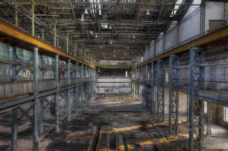 Light rays in a large abandoned production hall with an old crane